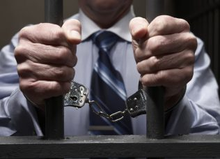 Man in handcuffs, holding prison bars, mid section, close-up of hands