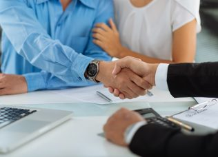 Close-up image of real estate agent and his client shaking hands